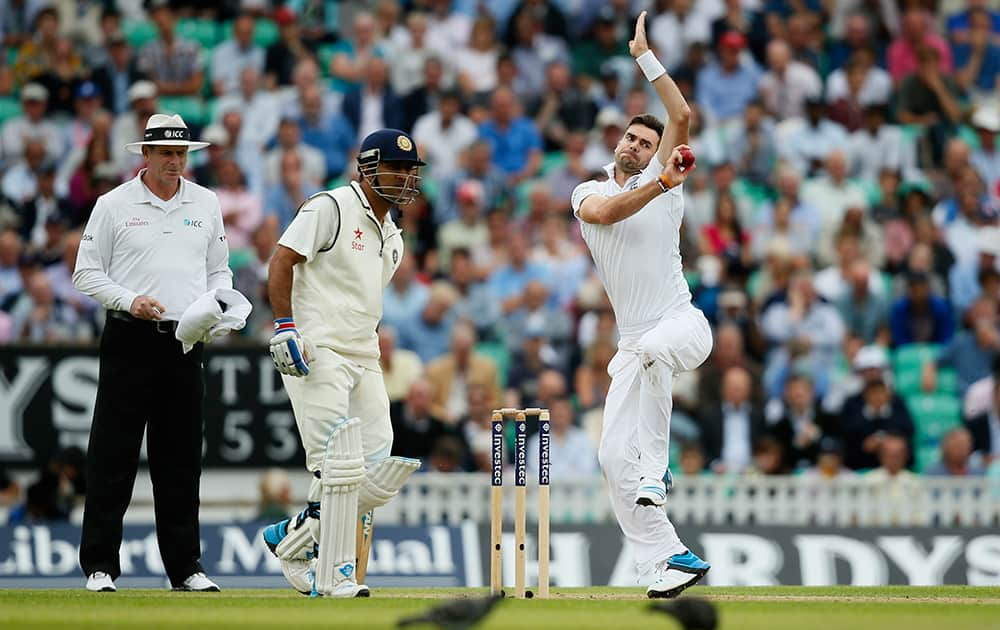 England's James Anderson, right, bowls to India's Stuart Binny during the first day of the fifth test cricket match at Oval cricket ground in London.