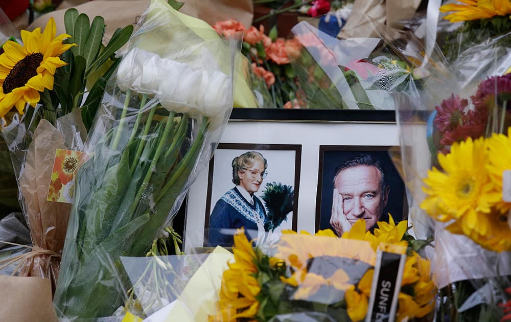 Flowers and photographs are displayed, in San Francisco, of a makeshift memorial for actor Robin Williams outside a home which was used in the filming of the movie `Mrs. Doubtfire.`