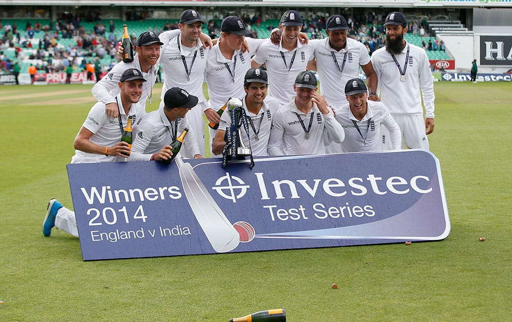 England cricket team Captain Alastair Cook holds the trophy as the team celebrate with champagne their 3-1 series win, after defeating India on the third day of the fifth test cricket match at Oval cricket ground in London.