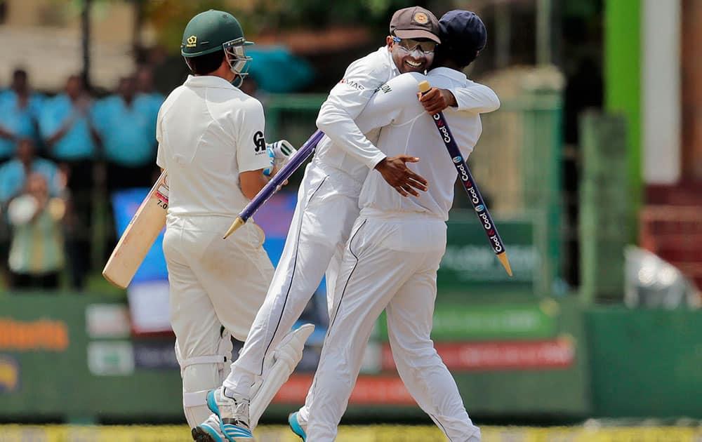 Sri Lanka's captain Angelo Mathews, right, lifts teammate Mahela Jayawardene as Pakistan's Saeed Ajmal walks off the field after Sri Lanka defeated Pakistan by 105 runs in their second test cricket match in Colombo, Sri Lanka.