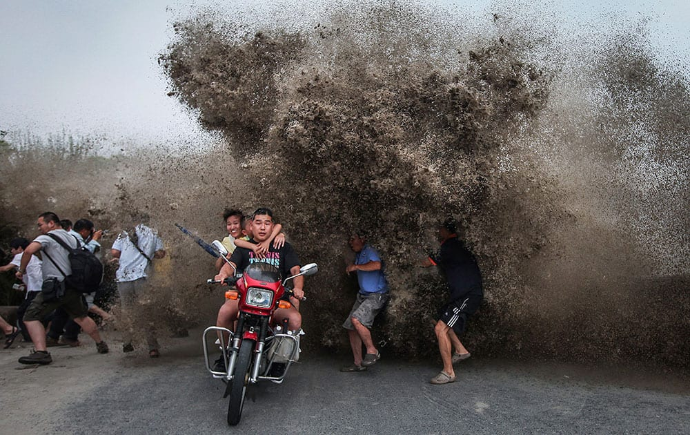 Bikers and spectators gathered to watch the Qiantang tidal bore run as a wave crashes inland on the banks of the Qiantang River in Hangzhou in east China`s Zhejiang province.