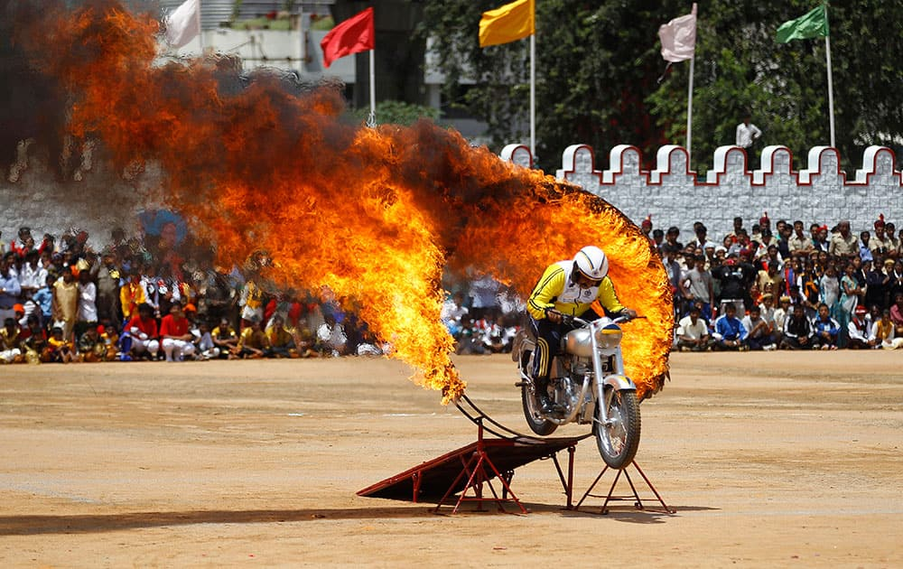 An Indian army officer drives through a burning ring as he performs a daredevil stunt during Independence Day celebrations in Bangalore.