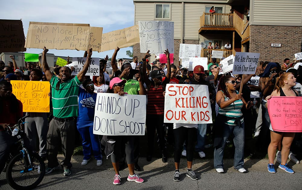 Demonstrators peacefully gather, at the site where Michael Brown was shot and killed by police in Ferguson, Mo.