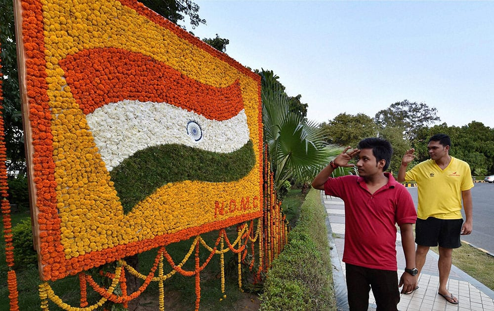 Two youth salute a Tricolor made with flowers on a display board at a pavement in New Delhi on the eve of Independence Day.
