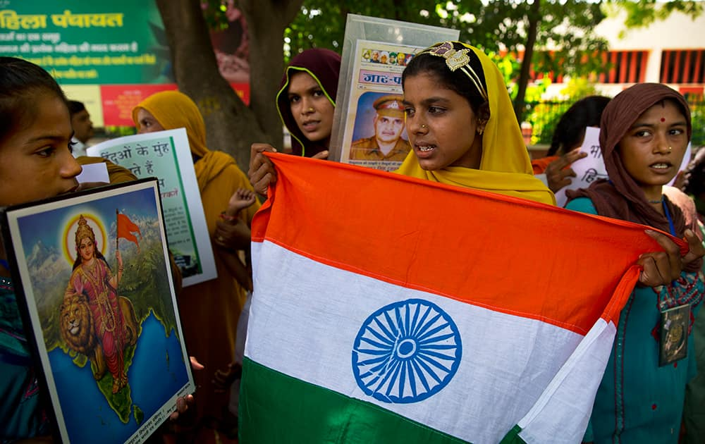 Hindu refugees from Pakistan who live in India hold the Indian flag and a picture of Mother India, left, as they gather for a protest on Pakistan's Independence Day in New Delhi.