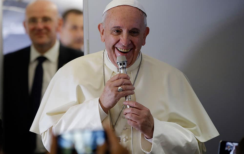 Pope Francis smiles as he meets journalists aboard the papal flight on the journey to Seoul, South Korea.