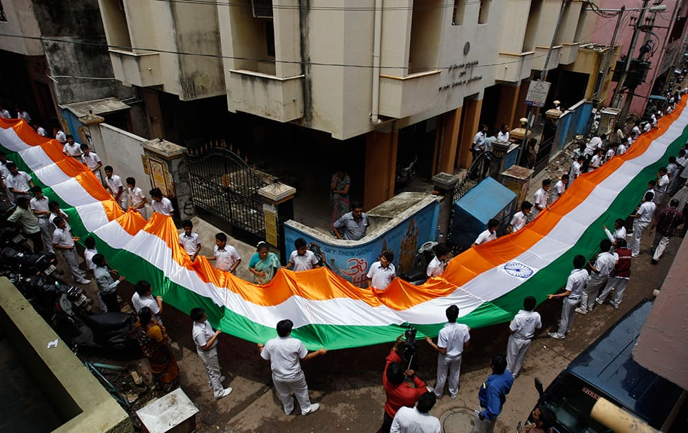 School children carry a 200 feet (61 meters) long Indian National flag through an alley as part of Independence Day celebrations in Chennai.