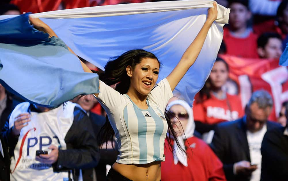 A performer holds an Argentine flag during a rally in support of the Argentine government in their dispute against a U.S. hedge fund, known as `vulture funds,` in Buenos Aires, Argentina.
