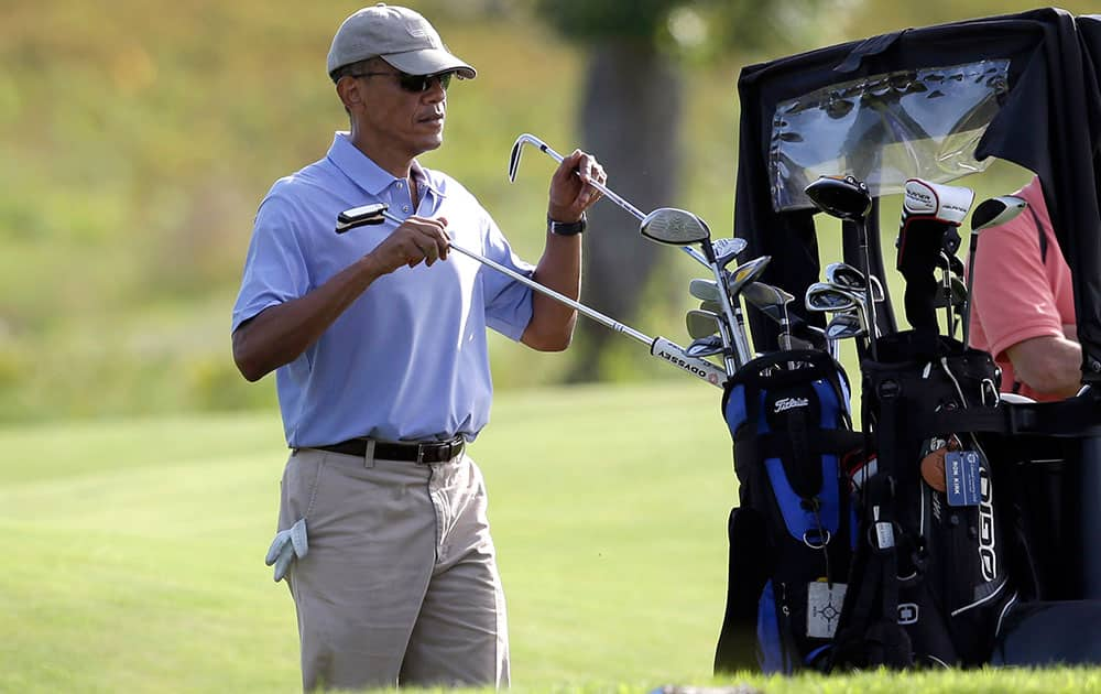 President Barack Obama returns clubs to the cart while golfing at Vineyard Golf Club, in Edgartown, Mass., on the island of Martha`s Vineyard.