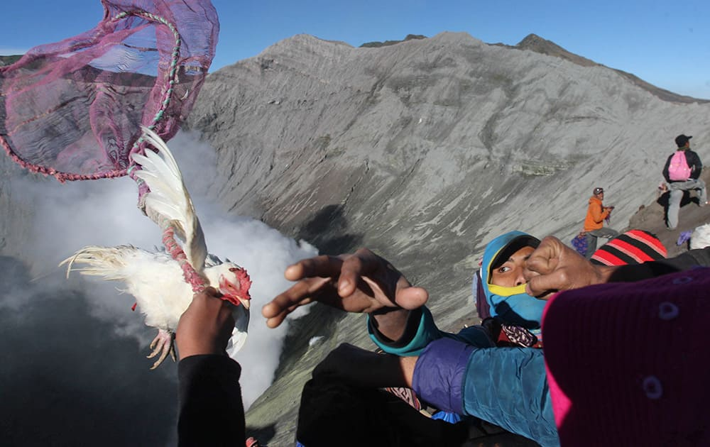 Villagers catch offering of a chicken thrown by Hindu worshippers into the crater of Mount Bromo in Probolinggo, East Java, Indonesia.