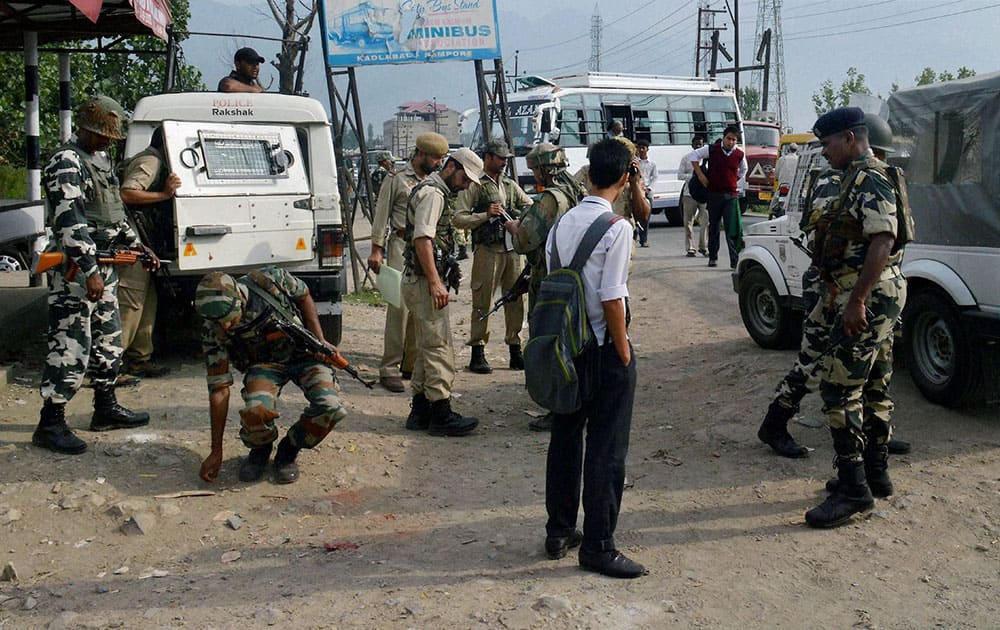 Army personnel inspecting on Tuesday the spot where a BSF convoy was attacked by militants on Monday evening near Pampore.