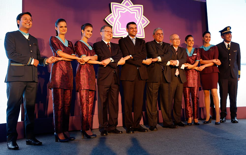 TATA SIA Airlines limited, crew members pose with their top officials from fourth left, Directors on Board Swee Wah Mak, Mukund Rajan, Chairman Prasad Menon and CEO Teik Yeoh, at a press conference to unveil the name and logo of the new airline' Vistara' in New Delhi.