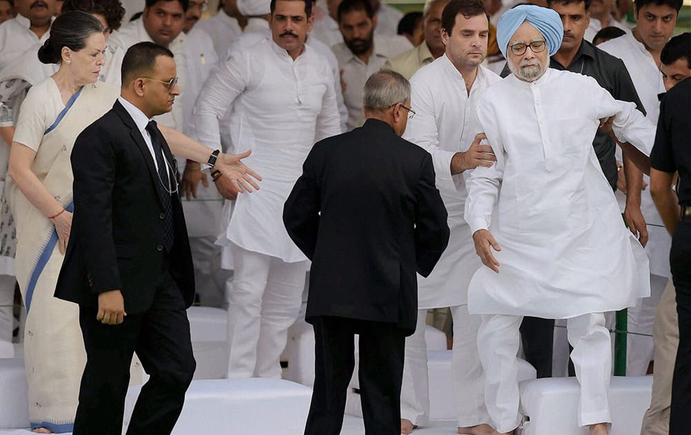President Pranab Mukherjee and Congress President Sonia Gandhi look on as Congress party Vice President Rahul Gandhi offers support to former Prime Minister Manmohan Singh after he stumbles during a function on former Prime Minister Rajiv Gandhi`s birth anniversary at Vir Bhoomi in New Delhi.