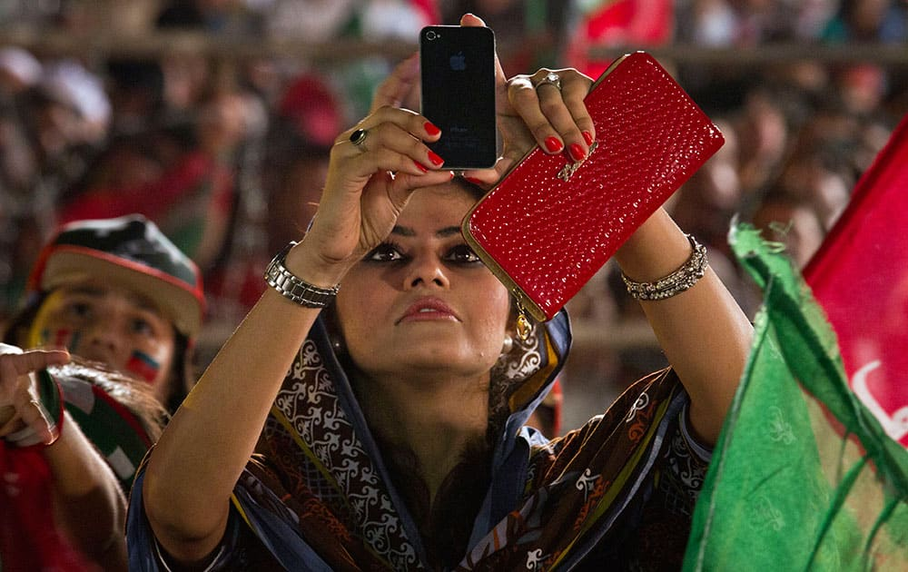 A supporter of Pakistan`s cricketer-turned-politician Imran Khan uses her cell phone to take picture of Khan during a protest near the parliament building in Islamabad, Pakistan.
