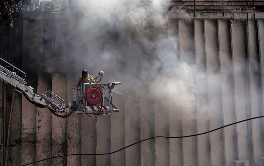 Fire officials douse a fire at a building in Connaught Place in New Delhi. No casualties have been reported so far and the cause of the fire is not known. Fire officials believe that the blaze broke out due to a short circuit in the electric wiring at the NIIT Center.