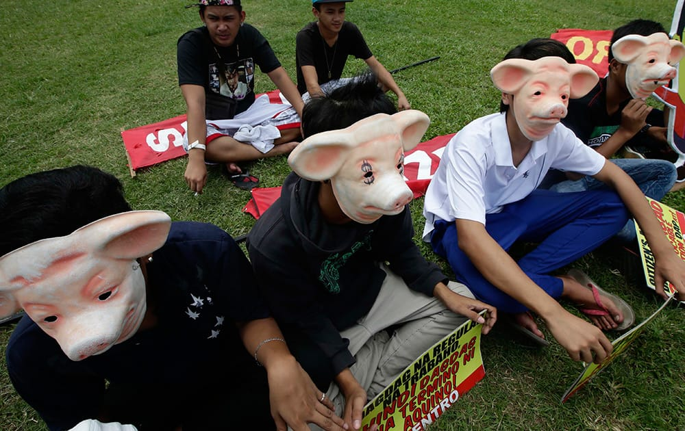 Protesters wear masks during a rally at Manila`s Rizal Park to demand the abolition of Government funds intended for the lawmakers to finance their projects known as `Pork Barrel Fund` in Manila, Philippines.