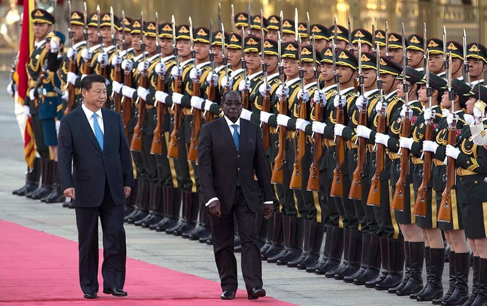 Chinese President Xi Jinping walks with Zimbabwe`s President Robert Mugabe during a welcome ceremony outside the Great Hall of the People in Beijing, China.