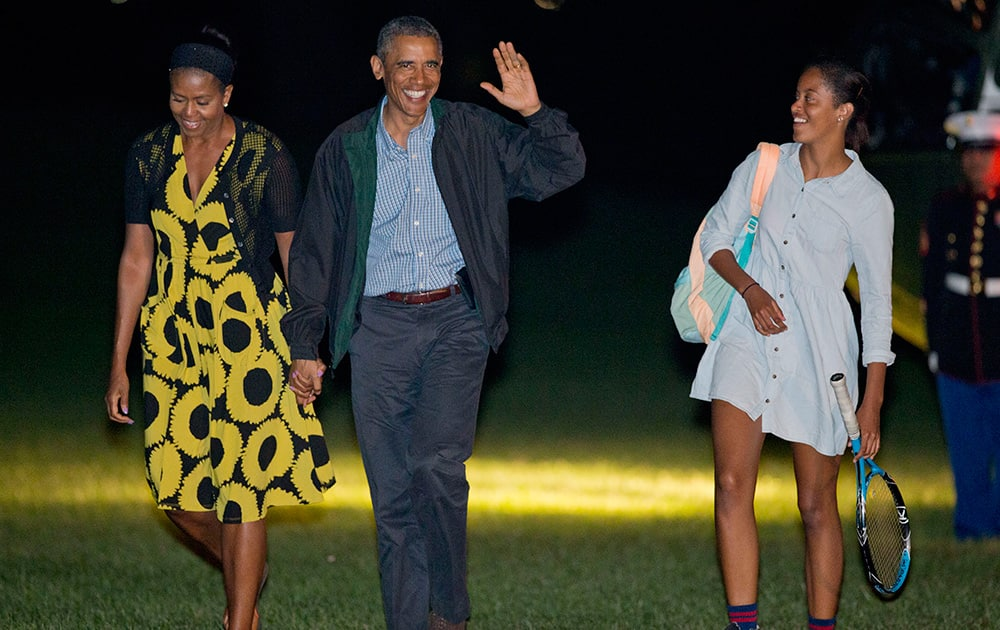 President Barack Obama and first lady Michelle Obama, walk with their daughter Malia, across the South Lawn of the White House in Washington, following their arrival on Marine One helicopter. Obama returned to Washington after spending two weeks with his family on the island of Martha`s Vineyard.