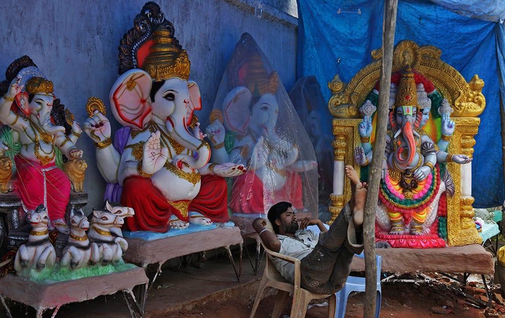 A vendor sits beside idols of elephant-headed Hindu god Ganesha as he awaits customers ahead of the Ganesh Chaturthi festival in Hyderabad.