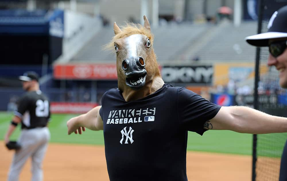 New York Yankees pitcher Shawn Kelley came out to stretch with a horse head mask on before a baseball game against the Chicago White Sox, at Yankee Stadium in New York.
