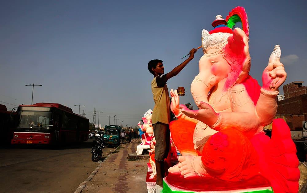 A artisan paints an idol of Hindu God Ganesha at an open workshop, ahead of Ganesha Chaturthi festival in New Delhi.