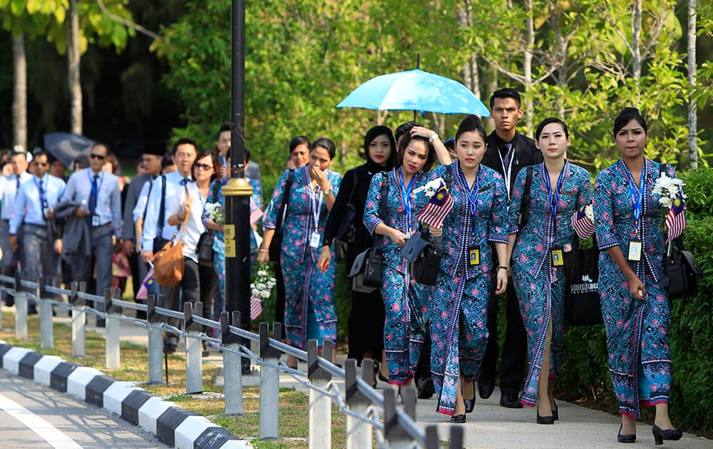 Malaysia Airlines crew members walk towards Bunga Raya Complex at Kuala Lumpur International Airport where victims` bodies of the ill-fated Malaysia Airlines Flight MH17 are flown back, in Sepang, Malaysia.