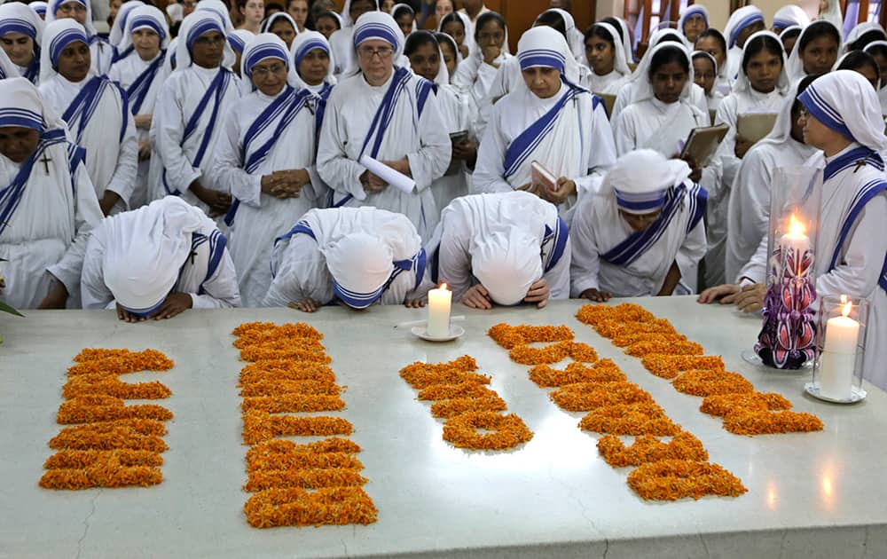 Nuns of Missionaries of Charity kiss the tomb of Mother Teresa during a mass on her birth anniversary in Kolkata.