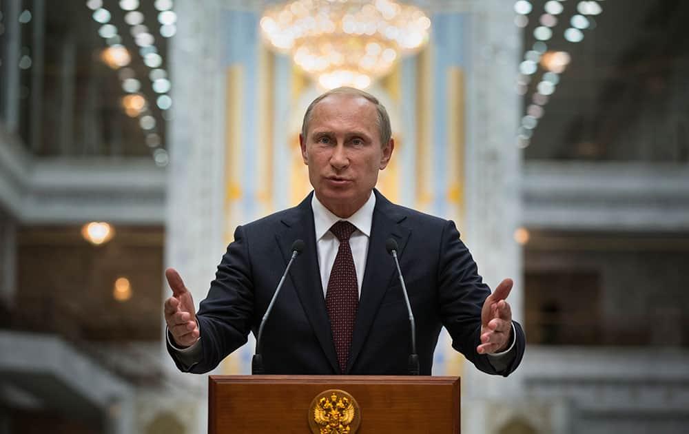 Russian President Vladimir Putin gestures as he speaks to the media after his talks with Ukrainian President Petro Poroshenko in Minsk, Belarus