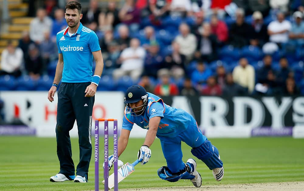 England's bowler James Anderson, left looks on as India's Rohit Sharma dives to make his crease, during their One Day International cricket match at the SWALEC cricket ground in Cardiff, Wales.