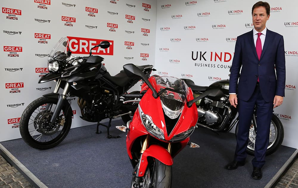 Britain's Deputy Prime Minister Nick Clegg poses with Triumph motorcycles during the inauguration of the United Kingdom India Business Council Centre in Bangalore.