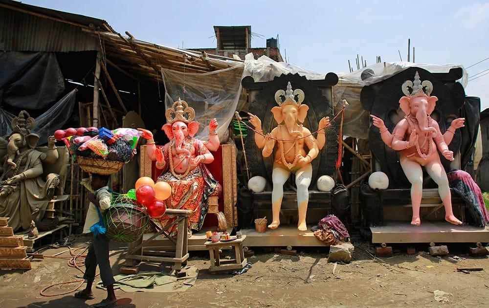 A vendor carries plastic goods and walks past idols of Hindu god Ganesha kept on display for sale ahead of Ganesha Chaturthi festival in Guwahati.