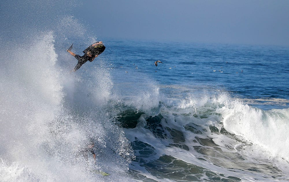 A bogieboarder flies over a wave a surfer rides underneatch a wave at the wedge in Newport Beach, Calif.