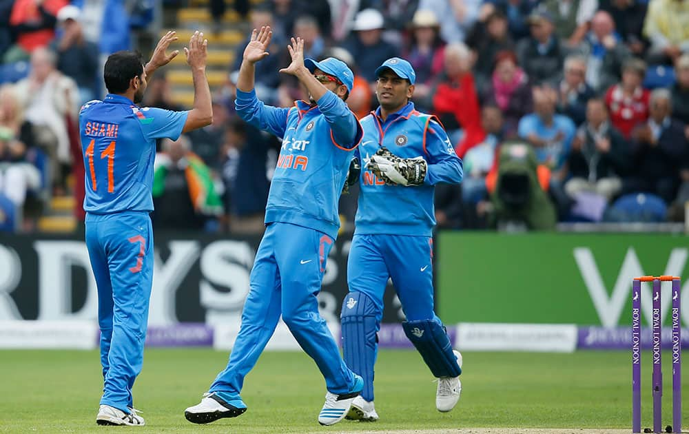 Mohammed Shami, left, celebrates taking the wicket of England's Alastair Cook, lbw, during their One Day International cricket match at the SWALEC cricket ground in Cardiff, Wales.