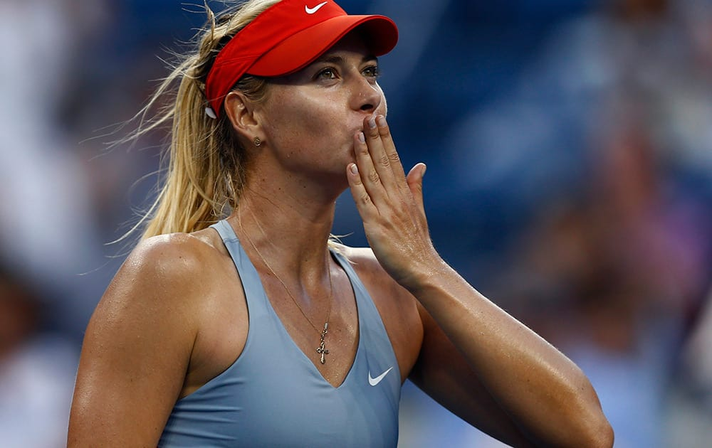 Maria Sharapova, of Russia, blows kisses to the crowd after defeating Alexandra Dulgheru, of Romania, during the second round of the 2014 U.S. Open tennis tournament in New York.