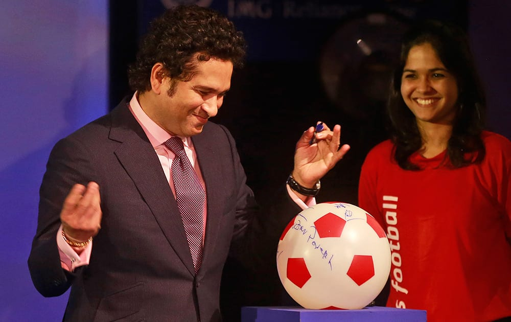 Sachin Tendulkar, former Indian cricketer and co-owner of Kerala Blasters Football Club, signs a soccer ball during official launch of the Indian Super League (ISL) in Mumbai.