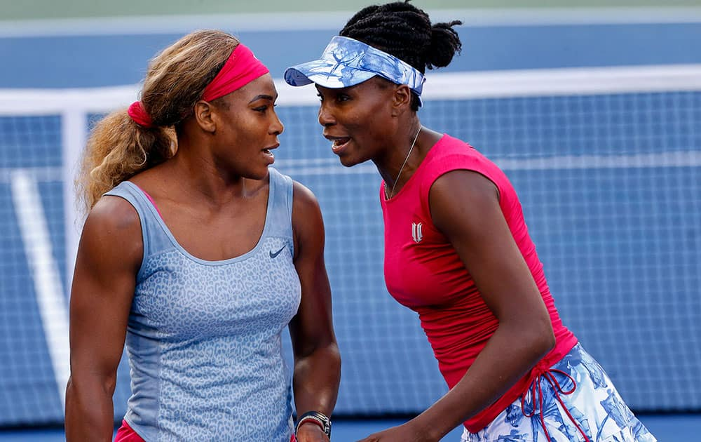 Serena Williams, left, and Venus Williams talk between points against Timea Babos and Kristina Mladenovic during a doubles match at the 2014 US Open tennis tournament.