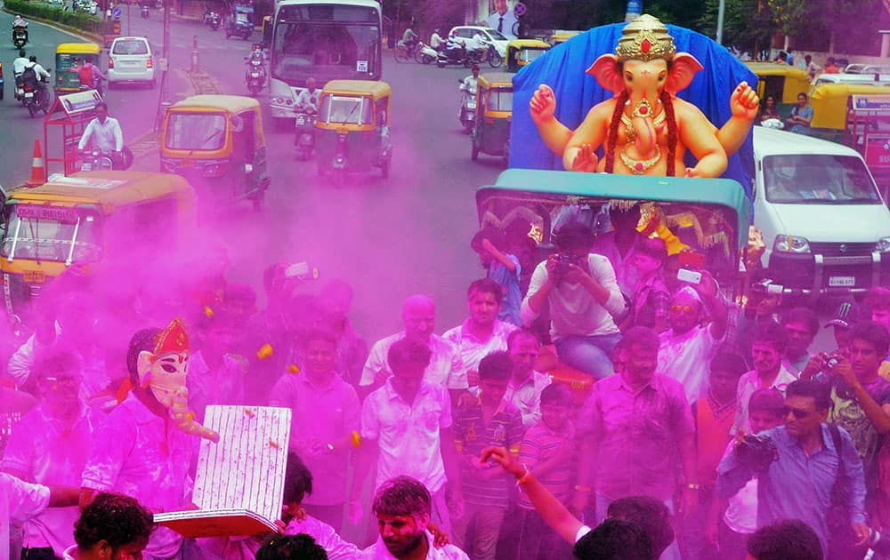 People throw colours at a Ganesh procession on the occasion of Ganesh Chaturthi in Ahmedabad.