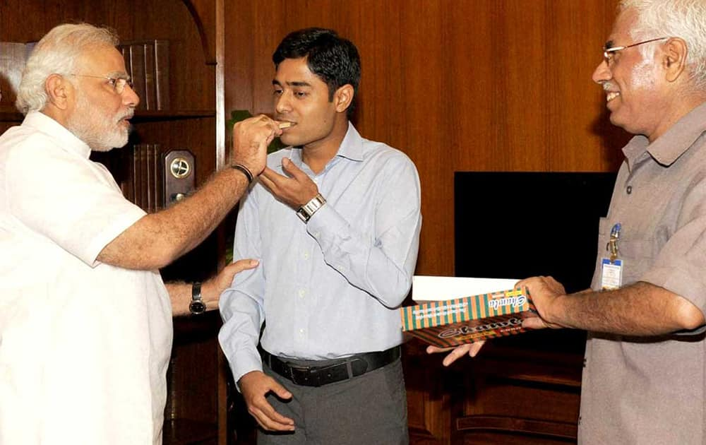 Modi greets the son of PMO staffer, Rajesh Kumar with sweets after he cleared the civil services examination.