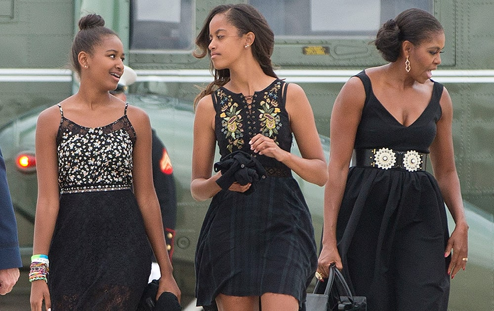 First lady Michelle Obama, right, and her daughters Sasha, left, and Malia, walk across the tarmac before boarding Air Force One prior to their departure from Andrews Air Force Base.
