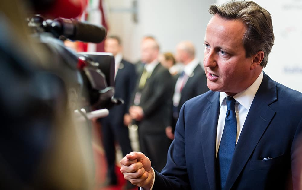British Prime Minister David Cameron talks with journalists at the end of an EU summit in Brussels.