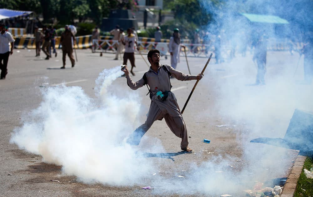 A Pakistani protester throws tear gas shell back towards police during a protest in Islamabad, Pakistan.