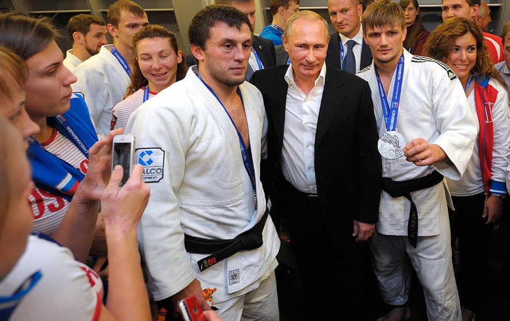 Russian President Vladimir Putin, center right, poses for a photo with athletes while attending the Judo World Cup in the city of Chelyabinsk in Siberia, Russia.