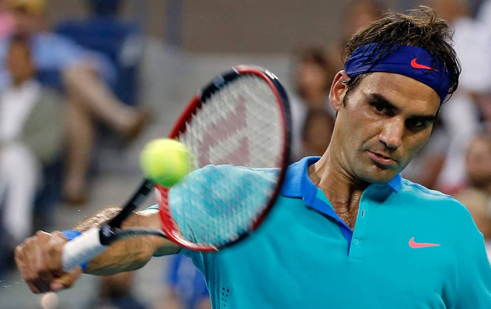 Roger Federer, of Switzerland, returns the ball against Marcel Granollers, of Spain, during the third round of the US Open tennis tournament.