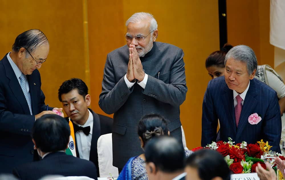 Indian Prime Minister Narendra Modi greets business leaders after giving a speech and returning to his seat as Chamber of Commerce and Industry Chairman Akio Mimura, left, and Japan Federation of Economic Organizations Chairman Sadayuki Sakakibara, right, greet him during a luncheon hosted by Japan Business Federation in Tokyo.