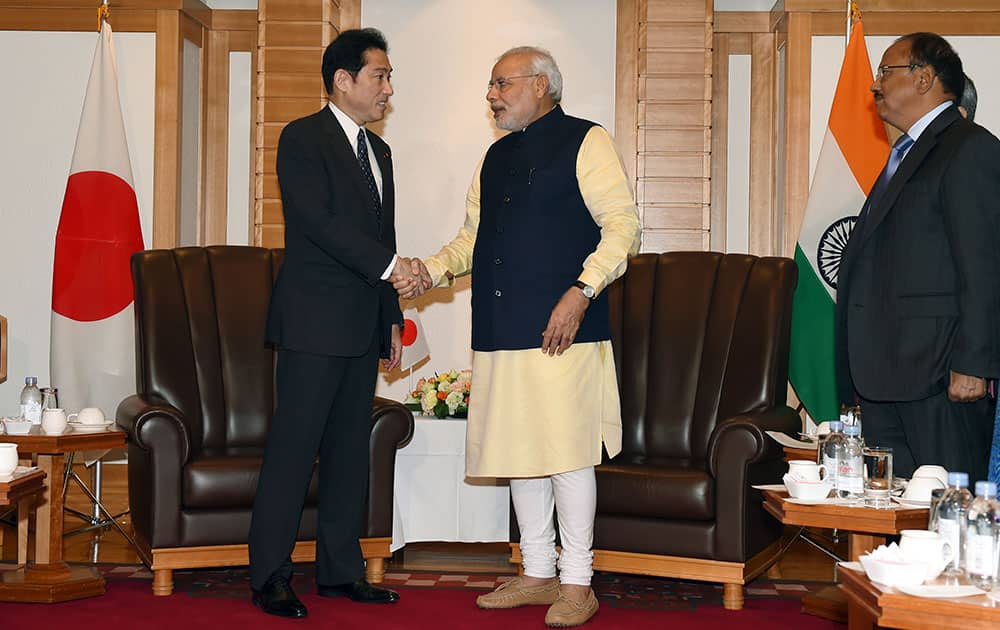 Indian Prime Minister Narendra Modi, center, is greeted by Japanese Foreign Minister Fumio Kishida, left, prior to their meeting at a Tokyo hotel.