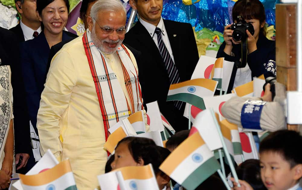Indian Prime Minister Narendra Modi is welcomed as he visits Taimei Elementary School in Tokyo.