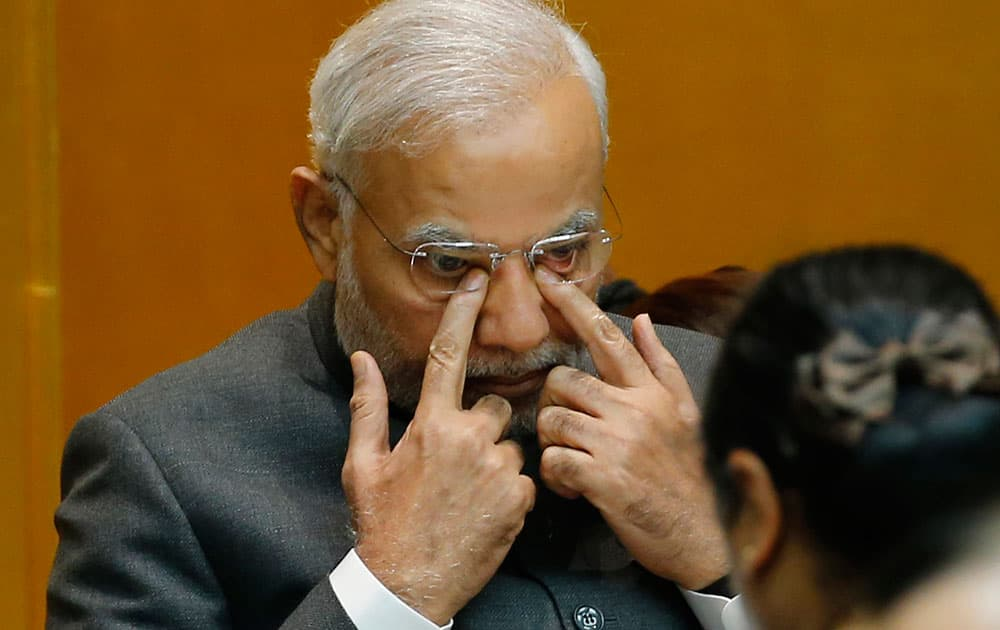 Indian Prime Minister Narendra Modi presses his eyes by fingers during a luncheon hosted by Japan Business Federation in Tokyo.