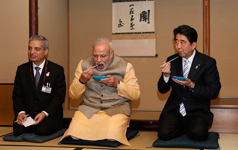 India's Prime Minister Narendra Modi, center, and Japanese Prime Minister Shinzo Abe, right, eat tea cakes during a tea ceremony at a tea hut of the Omotesenke, one of the main schools of Japanese tea ceremony, in Tokyo.