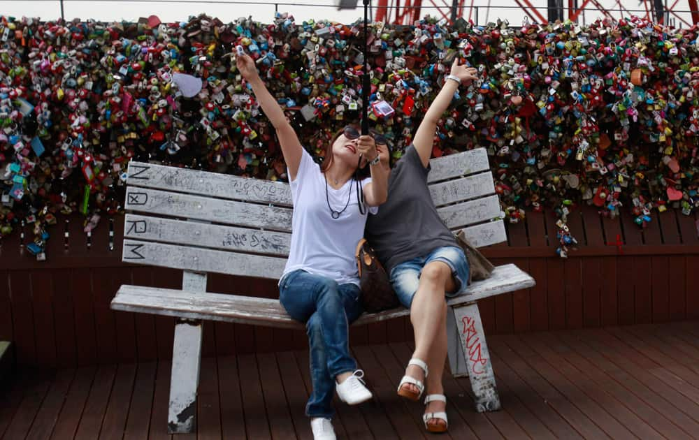 Visitors take a selfie on a heart chair on the roof terrace of N Seoul Tower in Seoul, South Korea.