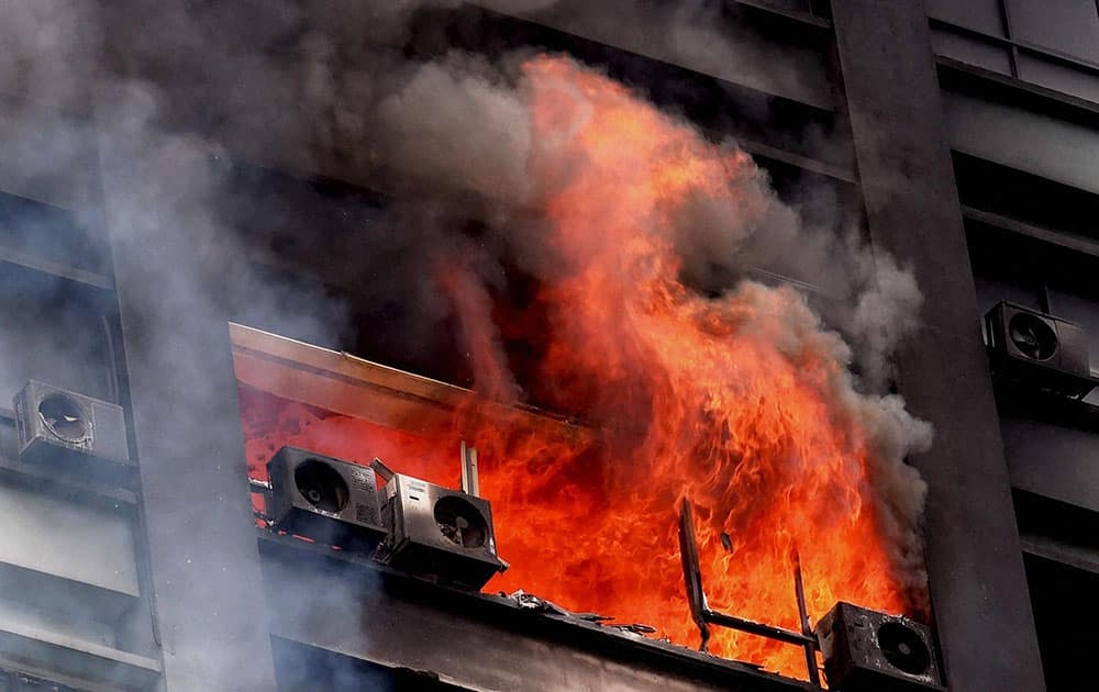Smoke and flames billowing out of a window after a fire at a building in Kolkata.